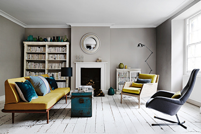 Modern living space with white ceiling and white wooden floor boards, grey walls and yellow modern sofa
