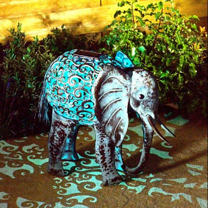 An outdoor elephant ornament with a solar powered turquoise ambient light