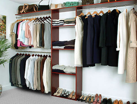Wooden open plan closet with shelves and three cloths rails
