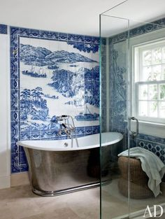 Traditional blue and white full wall tile art and vintage metal bathtub