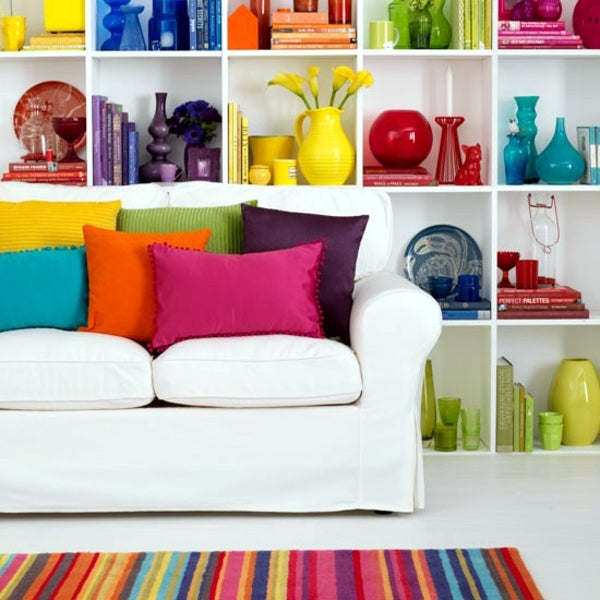 White sofa. with brightly coloured cushions, in front of white shelves with a different coloured object on each shelf