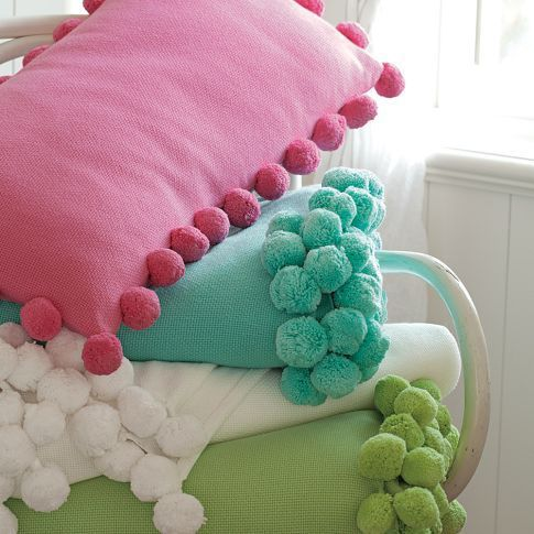 Different coloured cushions with a bobbled edge