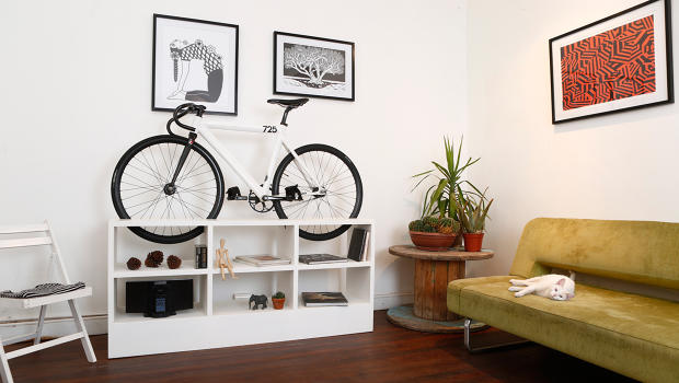 Bike Slotted On Top Of A Bookshelf, Where A TV Would Usually Be