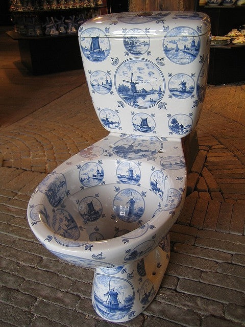 Blue and white china toilet on a stone floor in a showroom