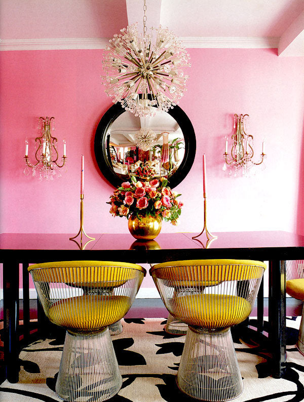 Bright pink walls with black dining table and unusual metal chairs with yellow seat pads