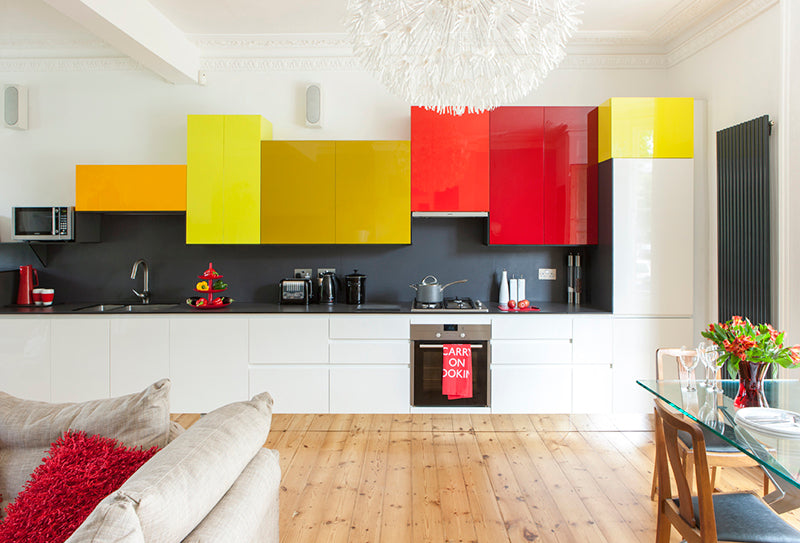 A white kitchen, with dark grey splash back and yellow, mustard and red unit doors