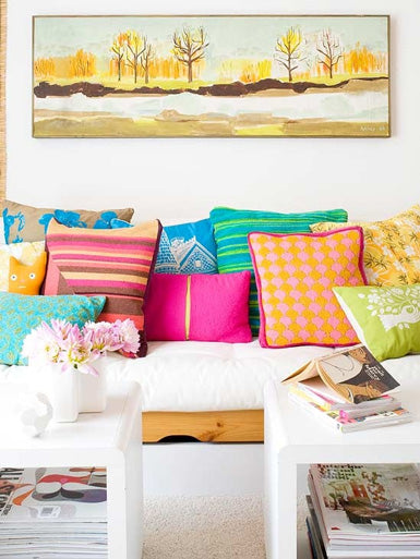 Lots of different coloured cushions on a white sofa, and wall art of a forest scene