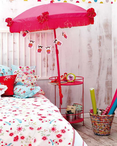 White and pink floral bedroom with indoor red umbrella and bedside table