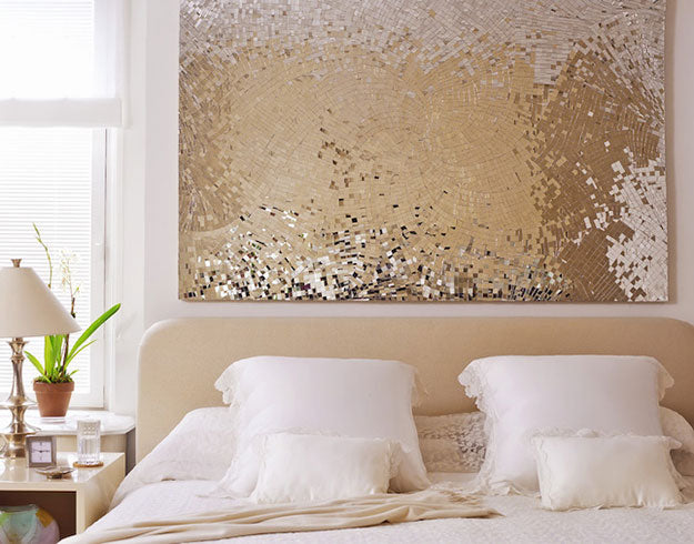DIY gold tile wall art above a white and cream double bed