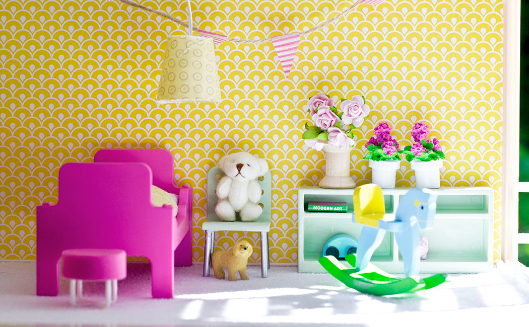 Yellow wallpaper in a dolls house with a fish scale type pattern, and small accessories