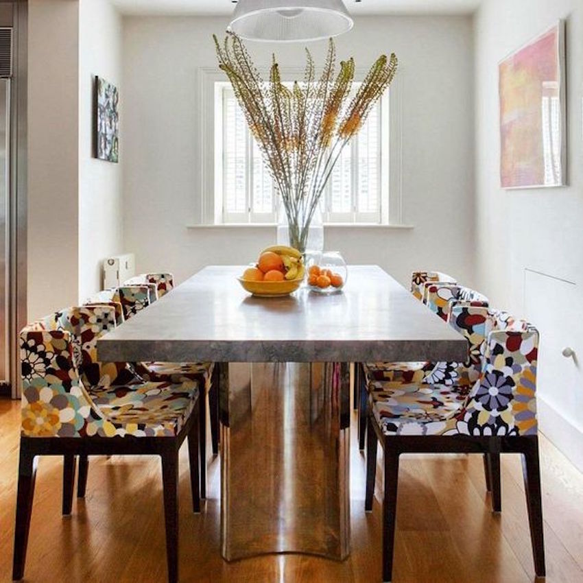 Marble table top, with fruit bowl and glass vase containing reeds, with modern patterned chairs
