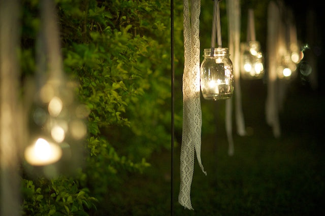 Glass Jars With Candles In Them Hanging From Trees
