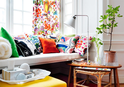 White living room with colourful eclectic throws, pillows and matching curtains