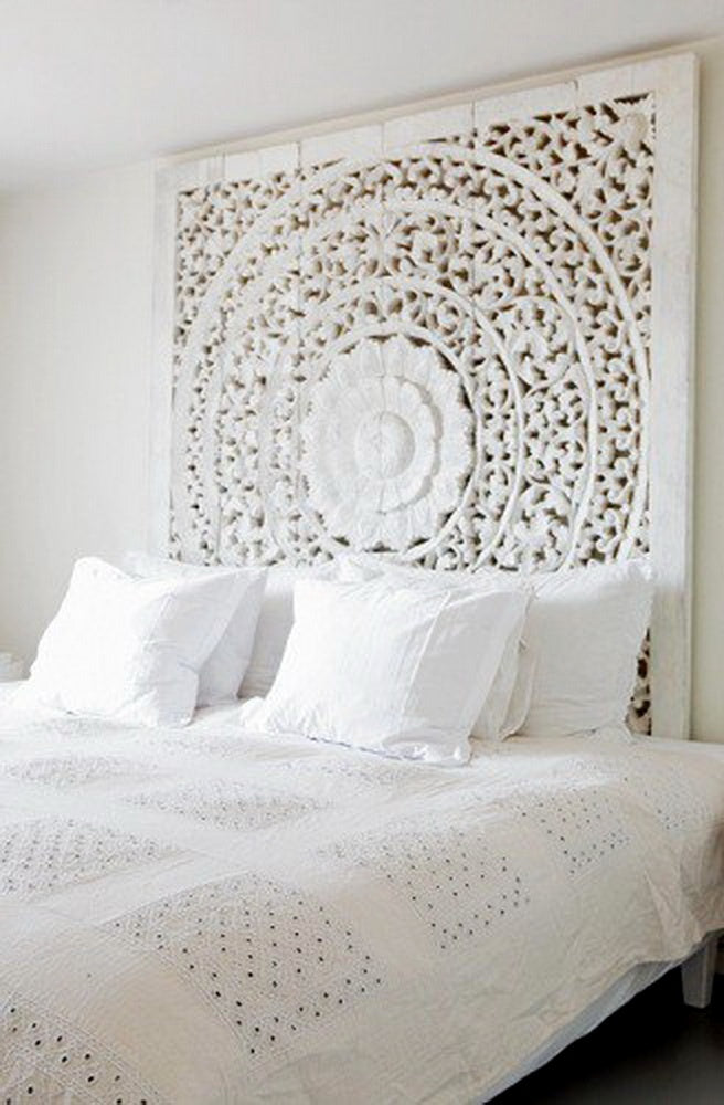 Intricate white round floral wooden headboard for a white bed