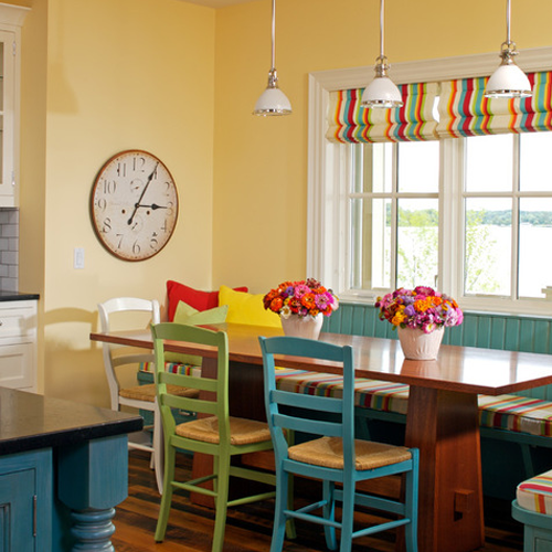 Pale yellow kitchen dining room with multi coloured roman blinds and wooden table in front of a light blue turquoise restaurant style seating bench