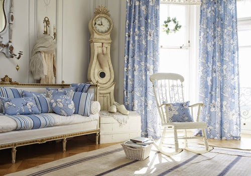 Cream and light blue living room with cream grandfather clock, light blue curtains and cream rocking chair