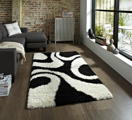 Black and white swirling patterned rug on a wooden floor
