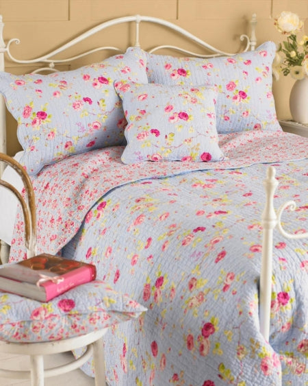 Blue and pink floral bedding on a white metal frame bed