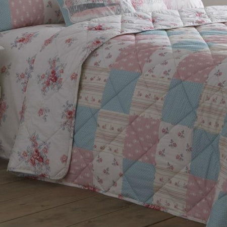 Pink, Blue And Cream Patchwork Bedspread Draped Over A Bed