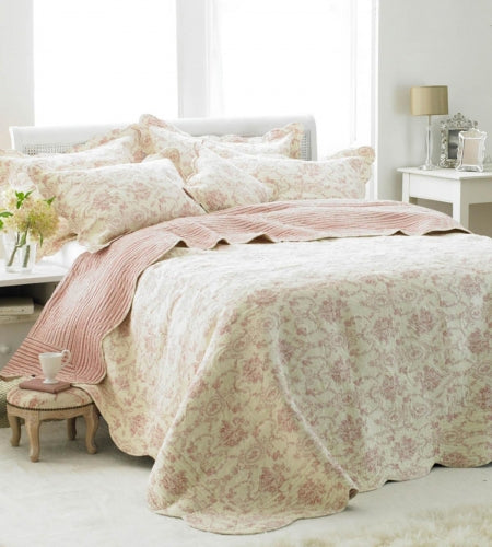Cream and subtle pink floral patterned bedding on a double bed