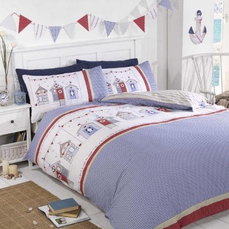 Blue, white and red beach hut style bedding, with bunting above the bed