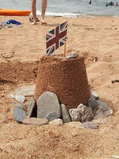A sandcastle on a beach with a union flag stuck in it
