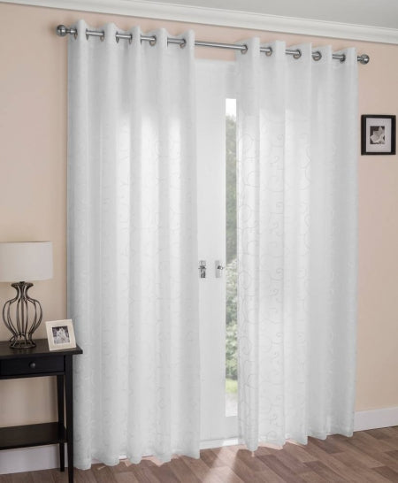 White eyelet voile curtains at a window