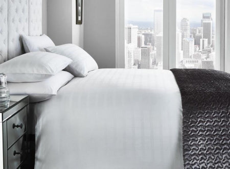 White bedding and bedroom with large windows overlooking a cityscape