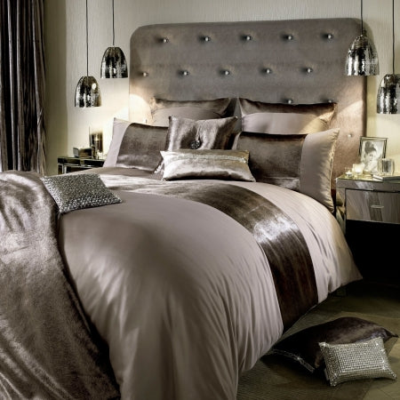Luxurious rich brown bedding on a large bed, with fabric headboard
