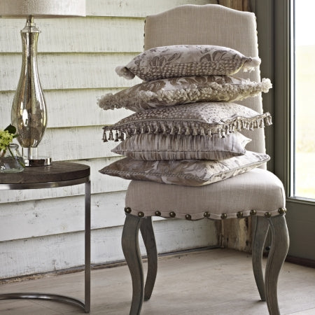 A stack of brown cushions on a beige chair