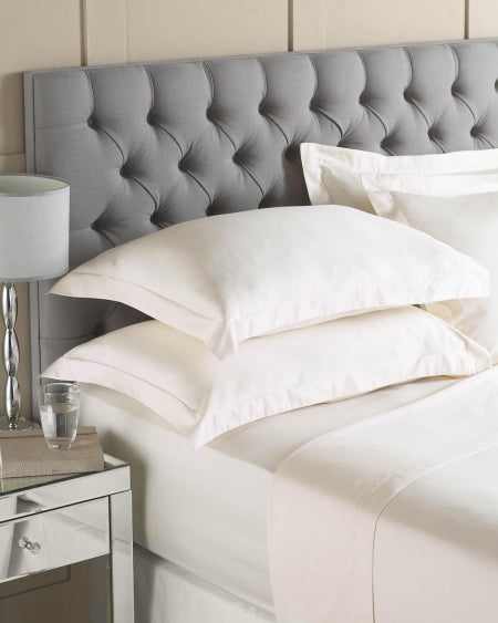 White bedding on a bed with a grey headboard