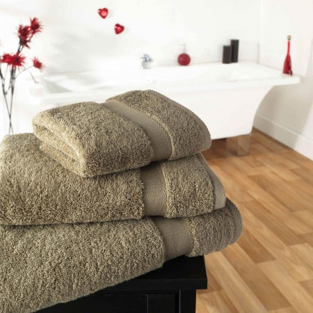 Beige towels piled up on a bathroom counter