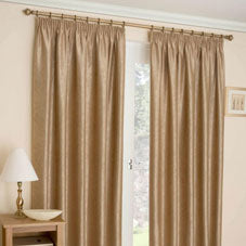 Dull gold pencil pleat curtains at a window