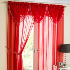 Red voiles hung at a window