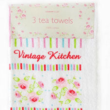 A kitchen tea towel in white with a cute pink, blue and green floral design