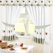 White kitchen curtains with a green trim and strawberry design