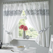 White kitchen curtains with a band of black at the top