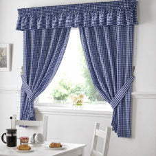 Blue kitchen curtains with a breakfast table in the foreground