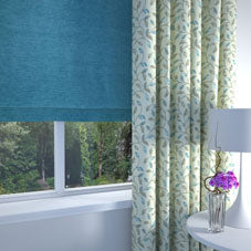 Cream and green intricate floral patterned curtains and a dark blue roman blind