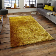 A plush yellow rug on a wooden floor