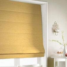 A yellow roman blind at a window