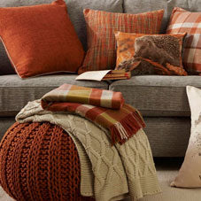 Orange cushions and a foot stool in a living room