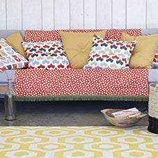 Red polka dot throw on a grey sofa, with cushions