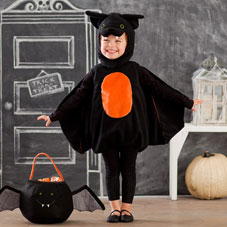 A young girl dressed a black bat