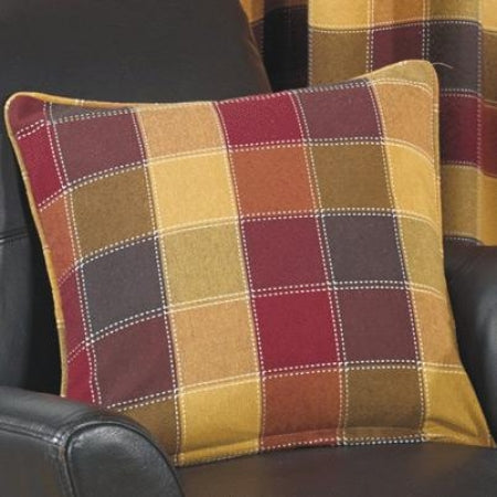 Checked red and gold cushion on a black leather sofa