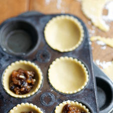 Uncooked pastry cases in cake mould, with mince pie filling