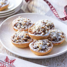 Fancy mince pies on a plate, decorating with icing sugar