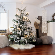 Lovely Christmas tree with white decorations, stood on a wooden floor