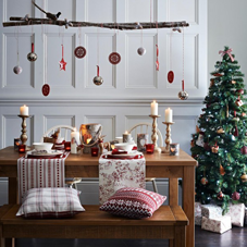 Lovely Christmas table setting with candles, and overhead branch decoration