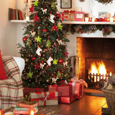 Lovely Christmas tree decorated in red and green, next to a roaring open fire